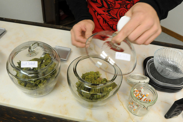 """Anthony Krepel, owner of Merry Janes Wellness Center replaces a bud of """"purple kush"""" into its container at the """"bud bar"""" during opening day of the medical marijuana dispensary."""