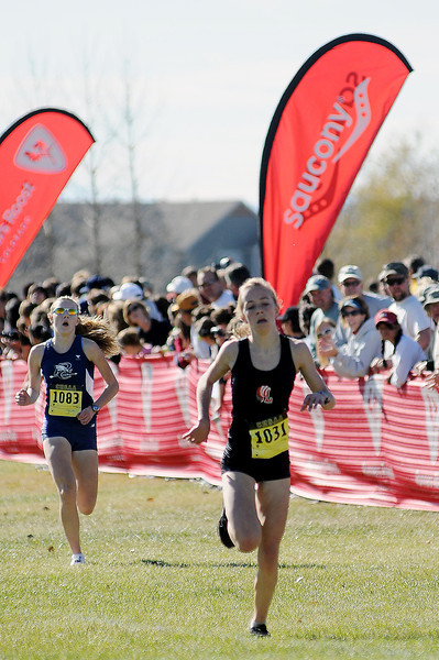 Loveland High School freshman Kailie Hartman, right, runs past Heather Bates of Pine Creek High School into fifth place in the 5A State Cross Country Championships on Saturday at Fossil Ridge High School in Fort Collins.