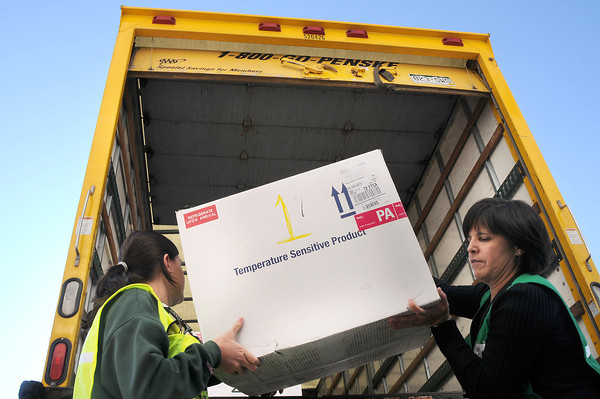 Larimer County Health Department workers Katie Sall, left and Sydney Gindler unload a box of the H1N1 vaccine before the start of the first Larimer County H1N1 flu clinic on Wednesday at The Ranch.