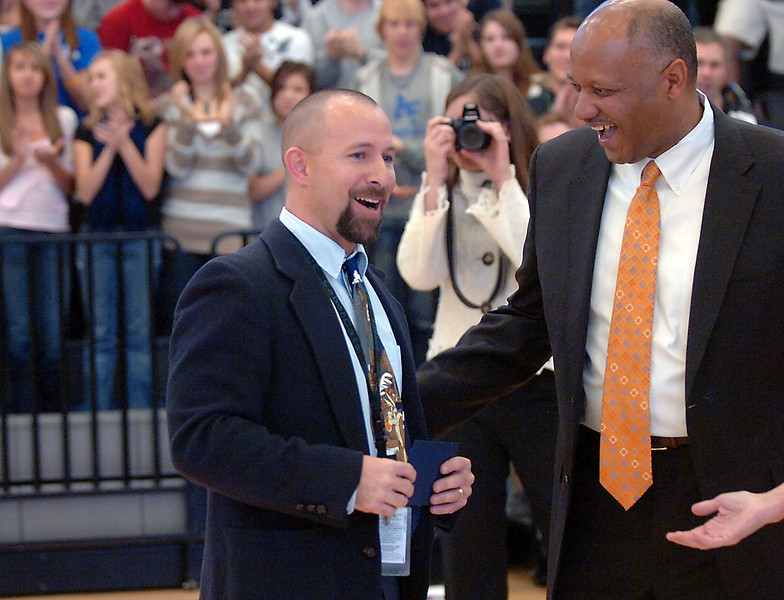 Fossil Ridge High School social studies teacher Mark Barry, left, is shocked to find out he is the recipient of the Milken National Educator Award Friday at the school in south Fort Collins. Dwight D. Jones, Colorado Commissioner of Education, right, congratulates Barry during an assembly to present him with the $25,000 prestigious award.