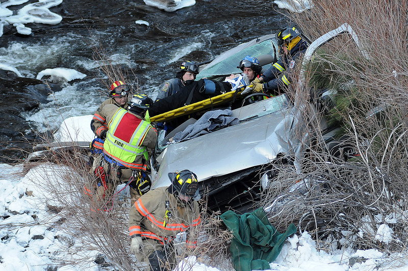 Members of Loveland Fire and Rescue and paramedics with Thompson Valley EMS work to free a woman after the car she was in plunged down the bank of the Big Thompson river on Monday evening near mile marker 79 on US 34. The woman and another person were in the car when it slid off the road and rolled to where it rested near the river. Emergency crews rushed to the scene after receiving a call after 3 p.m. According to crews on scene, the two were not in serious condition but were taken by ambulance to the hospital. Traffic was stopped in both directions while the crews worked to free the woman.