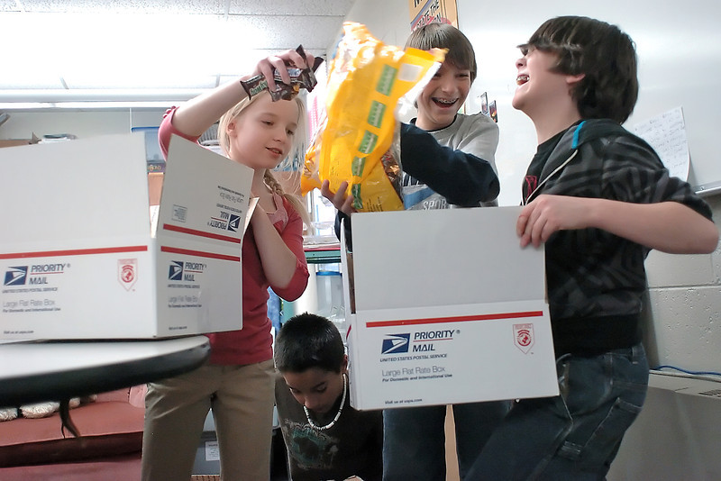 VanBuren Elementary School students fill care packages with items they collected that will be sent to American military members deployed in Afghanistan. At bottom is Tyrese Chavez, 9, and top from left are Hailey Greenup, 11, Lorenzo Scalise, 11, and Alex Moore, 10.
