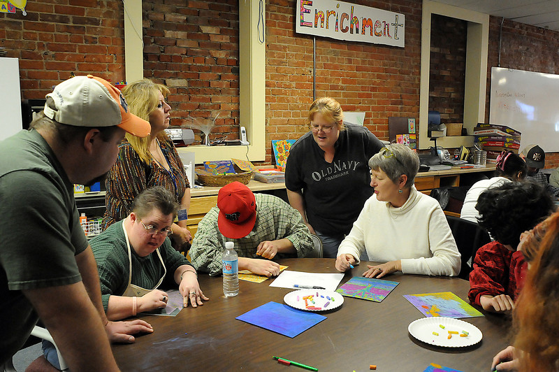 Volunteers, including Loveland artist Billie Colson, seated, second from right, at the Wings Center help clients make art on Wednesday afternoon. The support center for adults with disabilities will offer their 2010 calendar for $10 at the center, or they will ship it for $2.50 more.