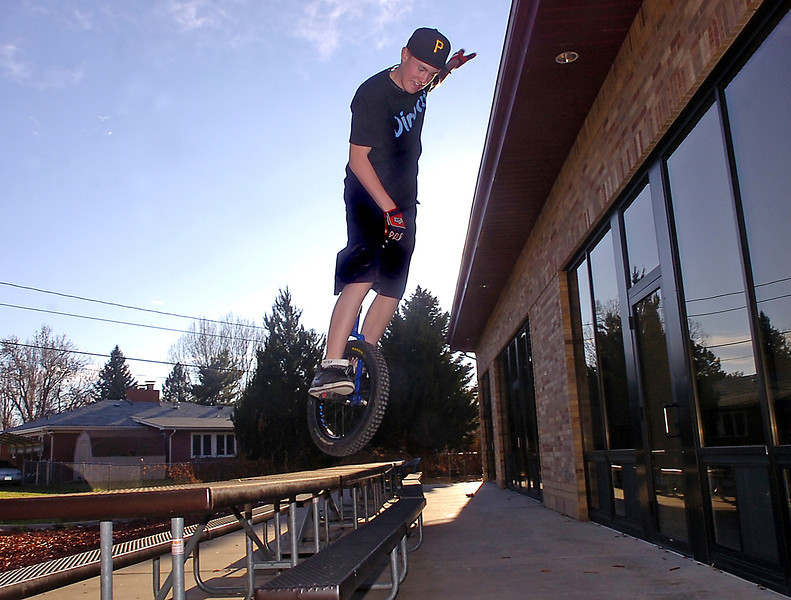 Sean Tait shows off some of his extreme unicycle riding as he jumps off of a picnic table near his Loveland home on Wednesday.