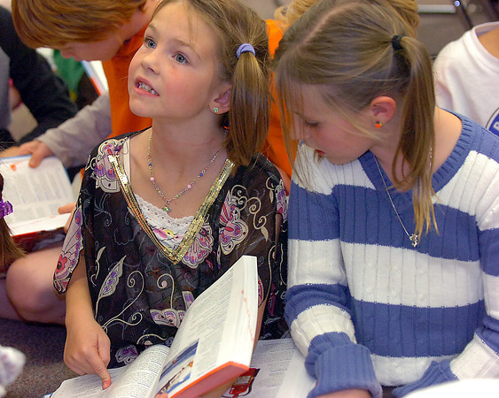 B.F. Kitchen Elementary School third grader Isy Omundson, 8, is excited to find the word respect in her new dictionary Friday at the school as her classmate Kaylee Echard, 8, right, looks on. Members of the Loveland Rotary Club and Medical Center of the Rockies Foundation gave third-graders at the school their very own dictionaries Friday.