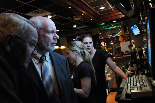 Mayoral candidates Glenn Rousey, left, and Dave Clark look at election results on the computer at the Pourhouse in downtown Loveland as bartender Jenna Gronberg, right, and manager Shannon Keramidis, work the bar on Tuesday night. The two candidates did not see the results they would have liked as rival candidate Cecil Gutierrez took the seatwith over 36 percent of the vote.