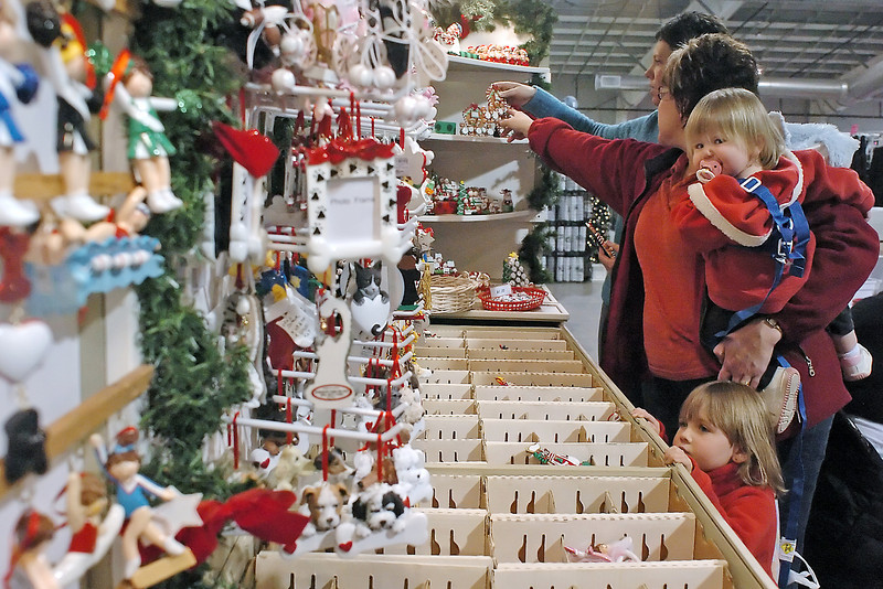 Kasey Weber, back, assists Loveland resident Jennifer Marchus as she shops for Christmas ornaments from Rascals with her daughters Siera, 1, and Makenze, 3, during the Applewood Arts at The Ranch arts and crafts festival on Saturday. The festival continues today from 11 a.m. to 4 p.m. with an admission fee of $4 for adults and children 12 and under free.
