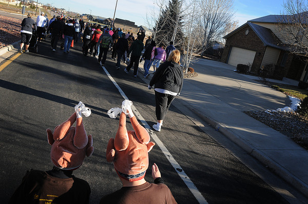 Ten-year-old friends Brady Mueller, left, and Peter Pryharski trot their way down North Boise Avenue in turkey hats on Thursday during the Loveland Turkey Trot.