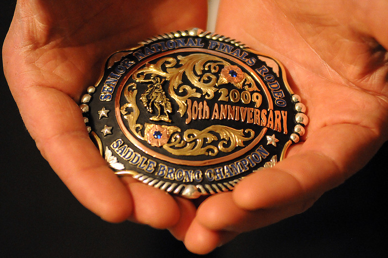 Saddle bronc rider Eddie Schmidt holds a trophy belt buckle from one of his three Championships. Schmidt knows his body can only hold out for another year or two but the 55 year old is proud of his accomplishments.