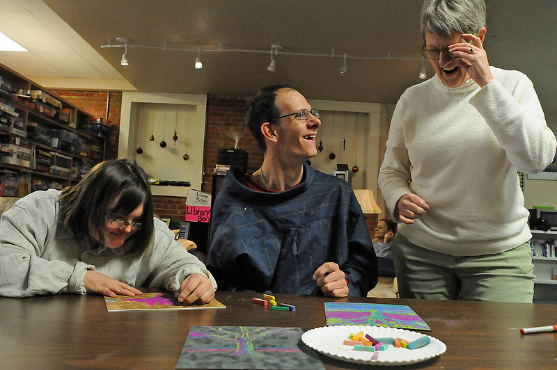 Loveland artist Billie Colson, right, talks with Wings Center clients Danny Soldner, center and Vanessa Cox as they team up to draw a tree on Wednesday. The center will offer their 2010 calendar for $10 if it is picked up at their building at 426 N. Lincoln Avenue in downtown Loveland.
