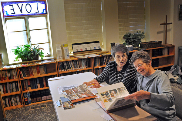 Sandy Hagberg, left, and Janice Gibb search through photographs on Thursday that they will include in a historical anniversary book of the First Presbyterian Church of Berthoud that will also include some of the member's memories.