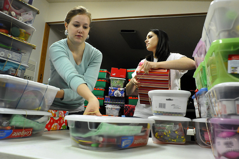 Operation Christmas Child volunteers Taryn McCaughey and Brooke Duncan help box up gift boxes for Operation Christmas Child on Thursday at Lifespring Covenant Church.