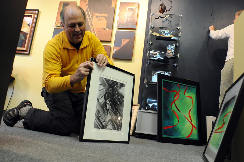 Photographer Bob Campagna adjusts a frame on one of his student's photos while hanging an exhibit with Independence Gallery owner Billie Colson, at right on Wednesday. The exhibit highlights the work of Thompson School District middle school gifted and talented student.