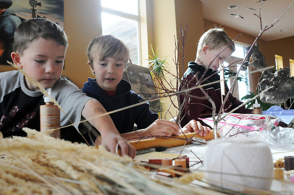 Six-year-old Devon Frisch, left, Jack Mandeville, 9, and Tyler Frisch, 8, build sculptures out of a variety of found and recycled items during a Green Adventures class offered through the Loveland Youth Gardeners called Thank You Planet Earth at the High Plains Environmental Center on Saturday.