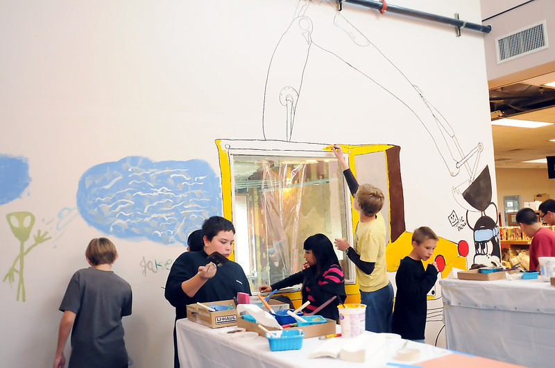 A group of youngsters paints a construction-themed mural on a temporary wall in the children's secion of the Loveland Public Library during a Teen Paint Party on Wednesday. Prior to painting the teens were treated to pizza and drinks.