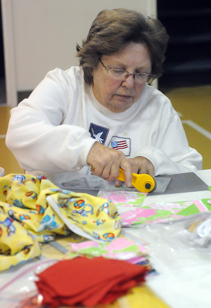 Judy Henderson cuts squares of material last Friday at Loveland Church of the Nazarene while volunteering with others to make quilts for the Warm Hearts/Warm Babies program.