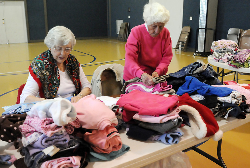 Betty Mathis, left, and Ella Mae Brewer sort and pack donated clothing for children last Friday in the fellowship hall at Loveland Church of the Nazrene last Friday. The clothing will be distrubuted to needy children.