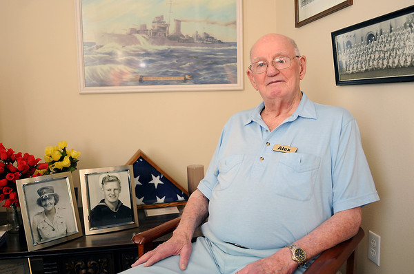 World War II veteran Alex Rothe poses in his Windsor home in front of a painting of one of the ships he served on during the war, and portraits of his wife, Lorraine, who was in the Marines, and himself in his navy uniform.