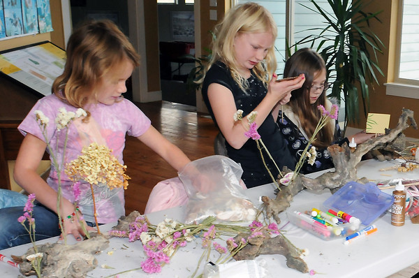 Youngsters use driftwood, flowers, seashells and a variety of other found and recycled items to build sculptures on Saturday morning at the High Plains Environmental Center. From left are Jordan Reichhardt, 7, Tasha Reichhardt, 9, and Chloe Entner, 10.