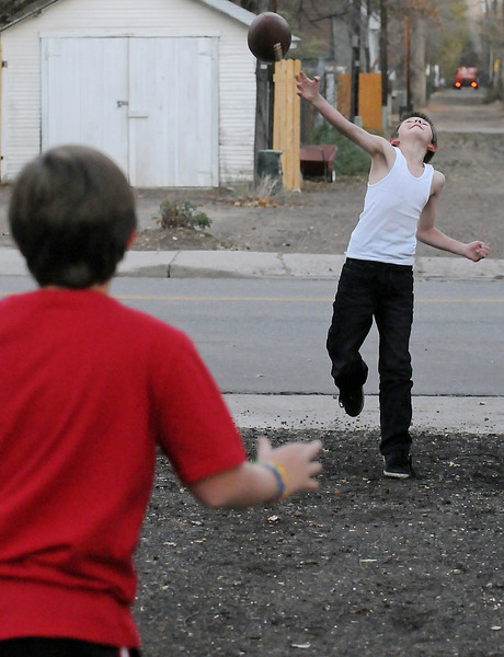 Nine-year-old Trevar Schmidt, right, throws a pass to Dilynn Cross, 9, while the friends play catch together Wednesday afternoon in downtown Loveland.