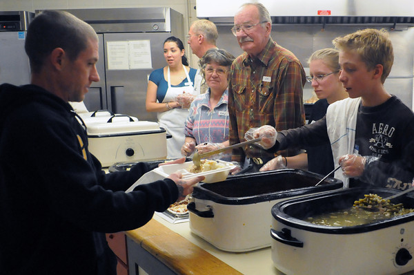 Delaware resident Will Carey, left, is served a meal at the Associated Veterans Club, 305 N. Cleveland Ave., on Thursday afternoon during the club's annual free Thanksgiving dinner event. Volunteering on the serving line are, from back left, Leanne Mathews, Jack Frost, Kathie Stephenson, Emmett Stephenson, Rebecca Weber, 16, and Jackson Engstrom, 13.