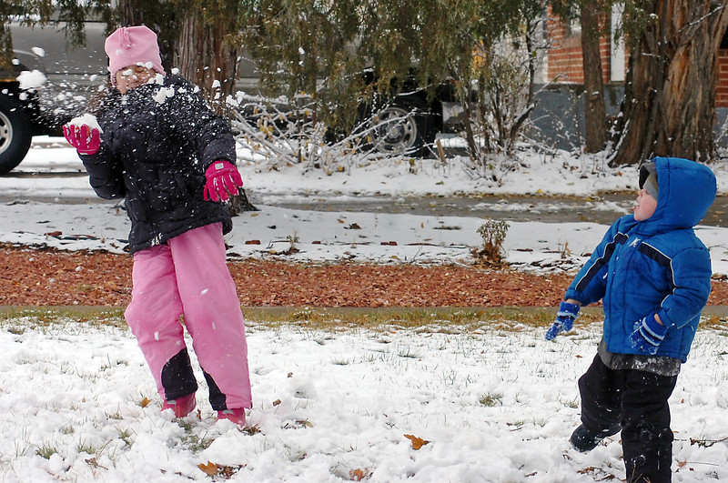 Tatum Gipson, 8, left, is showered with snow as a snowball thrown by her cousin, Angelo Sanchez, 4, strikes her shoulder as the two play together Thursday morning in the 1200 block of Garfield Avenue while waiting for the Veterans Day parade to begin.
