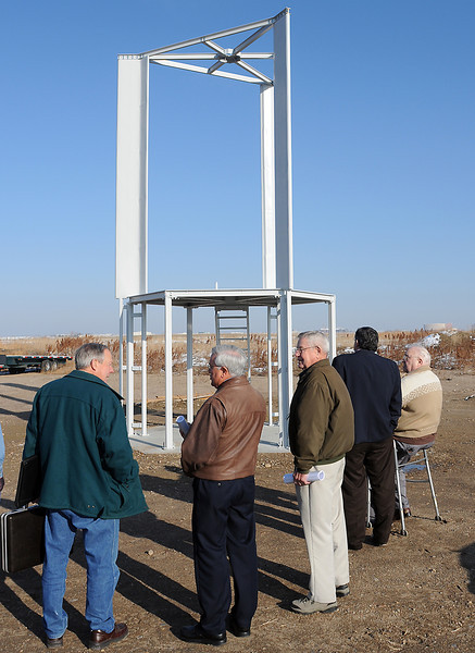 Presenters and attendees to a mini open house put on by Synchron Natural Energy Corp. on Friday at Cee-Jay Tool Co. stand beside the frame for a prototype Elder Vertical Turbine that will be used to produce electricity when completed. From left are Larry Simpson, Loveland Mayor Cecil Gutierrez, Del Wittler, Larimer County Commissioner Tom Donnelly, and Dillyn Elder, inventor of the Elder Vertical Turbine.