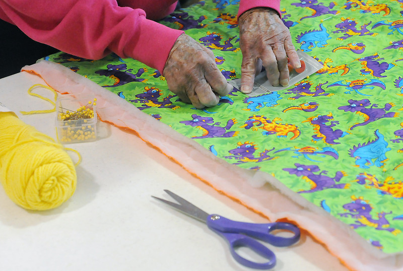 Ella Mae Brewer places push pins in a quilt to mark spots for attaching yarn to tye off the batting while volunteering with others last Friday at Loveland Church of the Nazrene to make quilts for babies for the Warm Hearts/Warm Babies program.