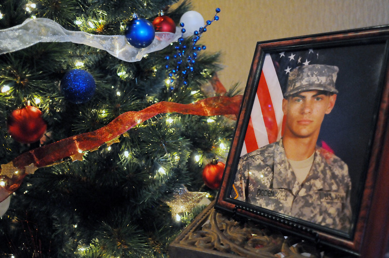 A portrait of Pvt. Dustin Ogden is on display next to a patriotic-themed Christmas tree decorated by employees from Century 21 Humpal, Inc. as part of the 2nd Annual Holiday Celebration of Trees at Embassy Suites.