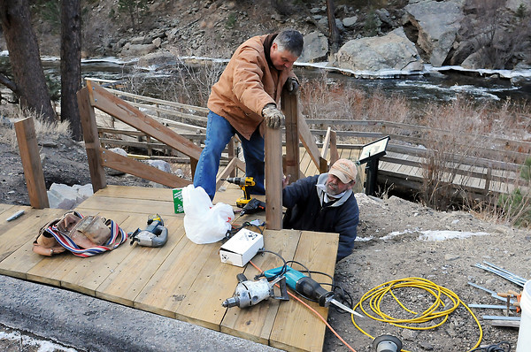 Dick Visintainer, left, and Dallas Maurer put the finishing touches on a stairway Saturday morning that leads down to a handicapped-accessible pier along the Big Thompson River east of Estes Park alongside U.S. Highway 34. Volunteers started work last May to replace the stairway and pier which had fallen into disrepair.
