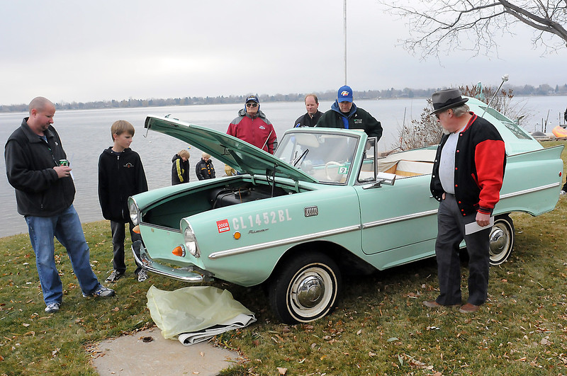 Loveland residents Justin Bue, left, and Alex Bue, 11, and others look at a 1967 Amphicar parked in the backyard of a house on the west side of Lake Loveland on Saturday morning before the car went up for auction. Justin claimed the car with a winning bid of $17,500 put in by his brother, Terry, who lives in Arizona.
