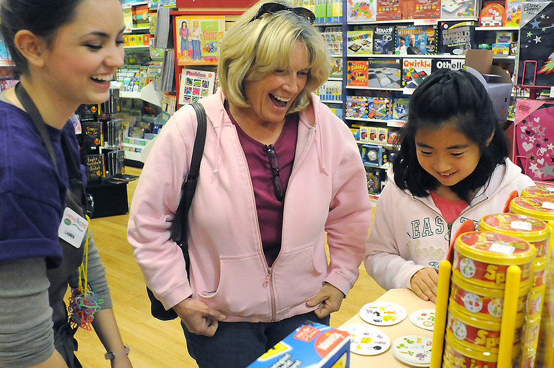 Learning Express supervisor Lauren Thompson, left, shares a laugh Thursday with Timnath resident Martha Martin and her daughter, Tori, 10, while playing the game Spot It! on display in the toy store located in the Front Range Village shopping center.