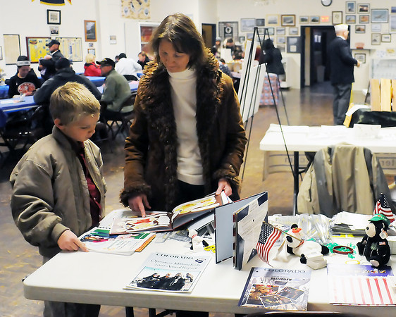Eight-year-old Keith Rasmussen and his mother, Jill, look at books on display Thursday at the Loveland Associated Veterans Club during the club's Veterans Day event. U.S. Army Sgt. William Rasmussen, Keith's father and Jill's husband, is currently serving overseas in Afghanistan.