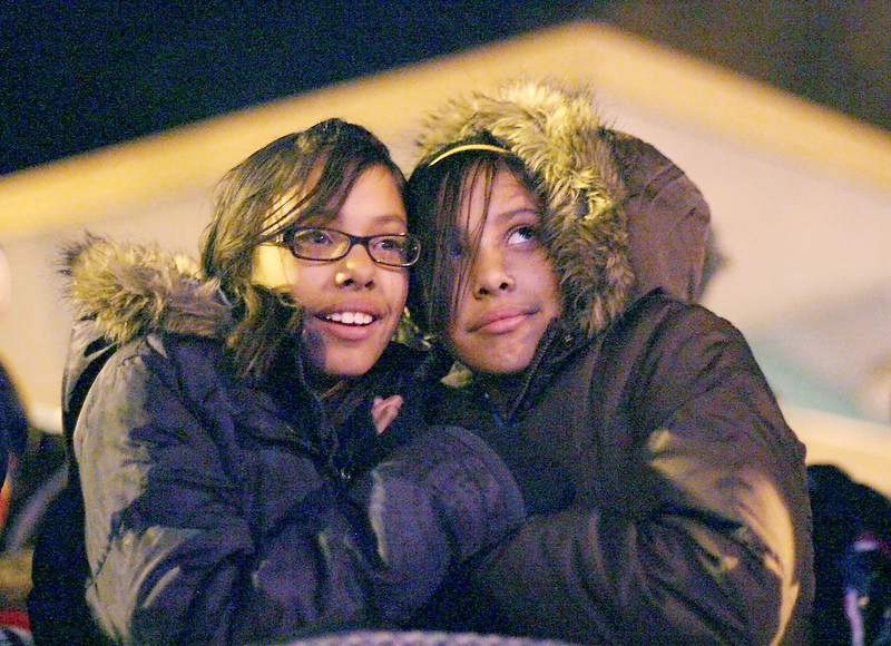 From left, Annie and Lexie Mendez, 11, watch the lights while trying to stay warm during the Loveland Community Tree Lighting sunday night in the Loveland Museum/Gallery parking lot. Photo by Gabriel Christus