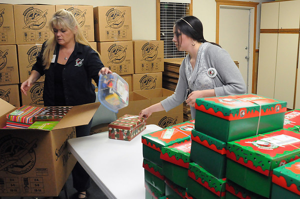 """LifeSpring Covenant Church volunteers Rene Wing, left, and Brooke Duncan pack gift boxes Tuesday evening in the chapel that were donated as part of Operation Christmas Child. The gifts contain items for 2- 14-year-old children and will be shipped to locations around the world. Donations are still being accepted of suggested gifts like school supplies, toys, personal hygiene items, flashlights, watches, t-shirts and socks. After placing the gift items in a standard-sized shoe box or plastic container they can be dropped off at the church, 743 S. Dotsero Drive, from 4-6 p.m. today through Friday, 10 a.m. to 2 p.m. on Saturday and noon to 3 p.m. on Sunday. A donation of $7 per box should be included to help cover shipping and other project costs. For more information visit  <a href=""""http://www.samaritanspurse.org"""">http://www.samaritanspurse.org</a> or call 667-4730."""