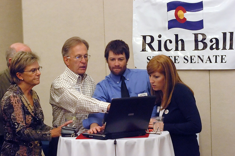 Colorado Senate Dist. 15 candidate Rich Ball, middle, and others look up election results on a computer Tuesday night during an election night party for Democrats at the Fort Colloins Marriott.