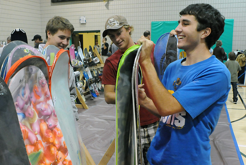 Loveland residents Sindre Andreassen, 17, left, Drue Hernblom, 17, and Ryan Winkelhake, 18, look through snowboards for sale during the 28th annual Ski and Sports Swap Friday evening at the Chilson Recreation Center. The event continues today from 8:30 a.m. to 2 p.m.