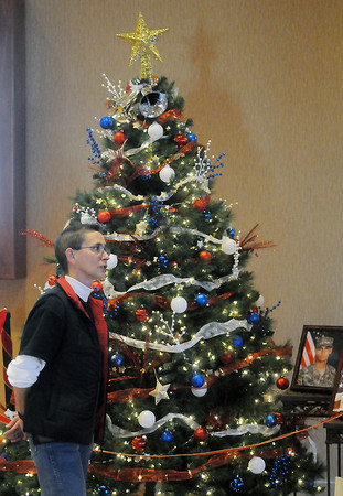 Jacklyn Ogden-Murphy talks about the Christmas tree decorated by Century 21 Humpal, Inc. employees in honor of her son, Pvt. Dustin Ogden, who is serving in the U.S. Army. The patriotic-themed tree is one of 20 on display during the 2nd Annual Holiday Celebration of Trees which runs through Dec. 11 at Embassy Suites.
