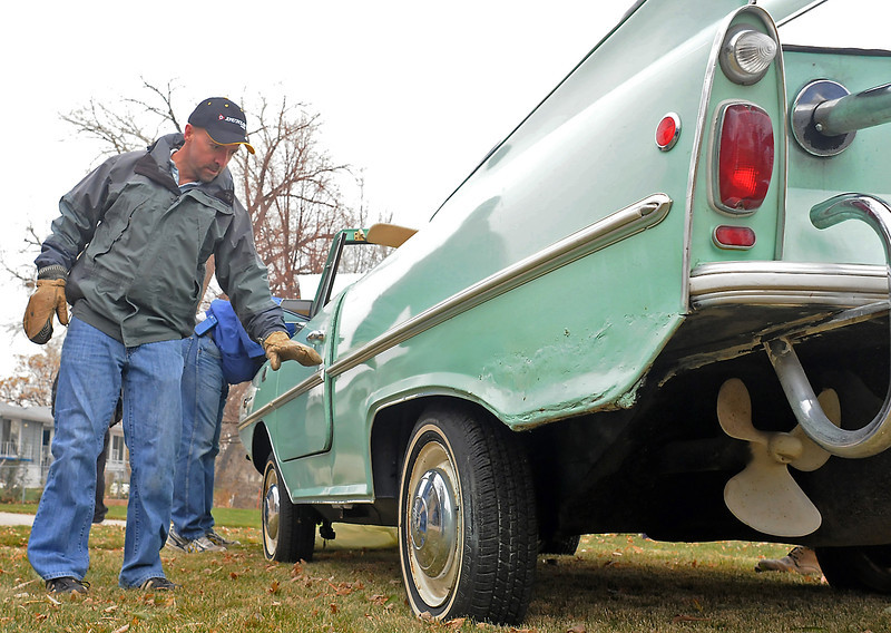 Loveland resident Rob Woodward, left, looks at a 1967 Amphicar parked in the backyard of a house bordering the west side of Lake Loveland on Saturday before the car was put up for auction.