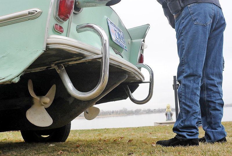 A man looks into the engine compartment of a 1967 Amphicar on Saturday morning next to Lake Loveland before the car went up for auction. The car features twin propellers at the rear and was made to run on land an water.
