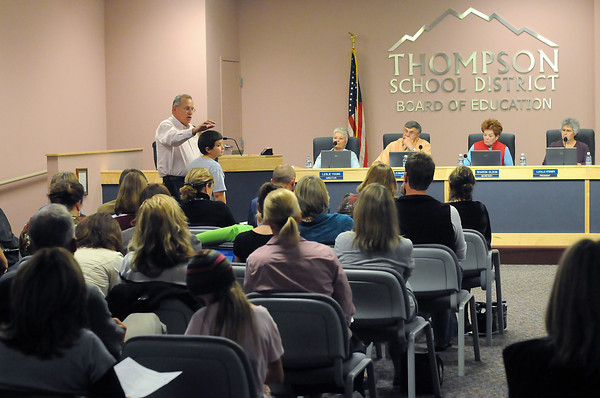 Alan Archer stands with his son, Marc, 10, while addressing Thompson School District board members during their meeting Wednesday as they listen to public comments on the Loveland Classical Schools charter application.
