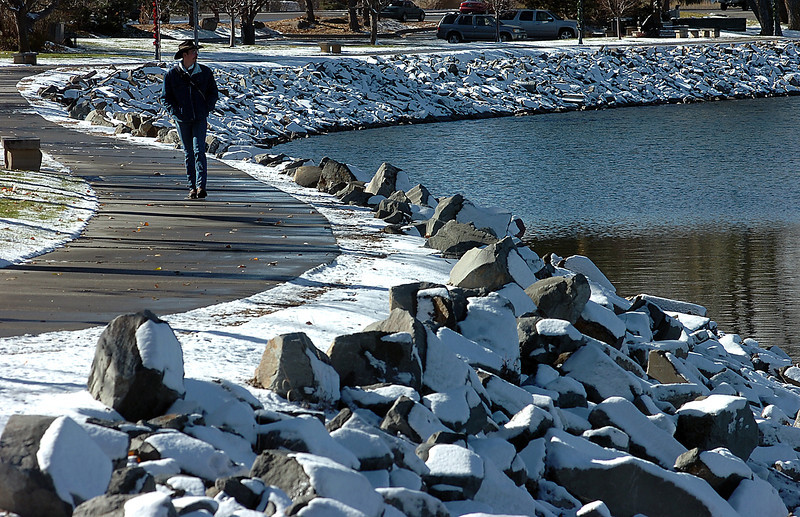 "A dusting of snow covers the rocks on the south sore of Lake Loveland Monday morning as Matthew Ward of Loveland enjoys a walk around the lake. Ward said ""If it were any warmer I'd be weraing my flip flops"" when talking about the weather."
