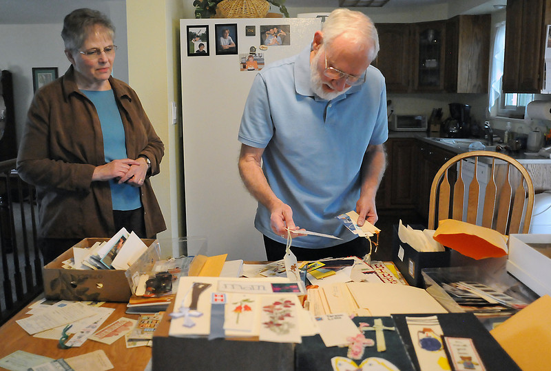 Barbara Franke looks on Tuesday while her husband, George, sifts through a collection of items found in books donated to Friends of the Library book sales over the years.