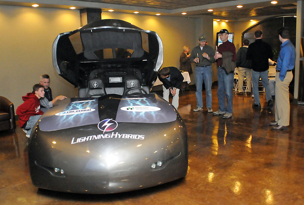 Reid Maynard, 15, left, and his father, Tom, look at a hydraulic hybrid sports sedan on display in the showroom are of Lightning Hybrids during an open house Friday evening at the company's new location in downtown Loveland at Mercury Plaza, 319 Cleveland Ave. Reid said he's interested in engineering and that he and his father have been interested in the new technology Lightning Hybrids is developing.
