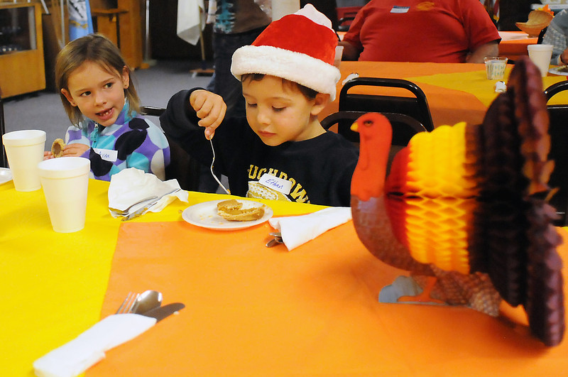 Anna Doyle, 7, left, and her brother, Ethan, 5, eat desert items together Thursday at the Associated Veterans Club, 305 N. Cleveland Ave., after volunteering to serve food with their parents, Karen and Mike, during the club's free Thanksgiving dinner event.
