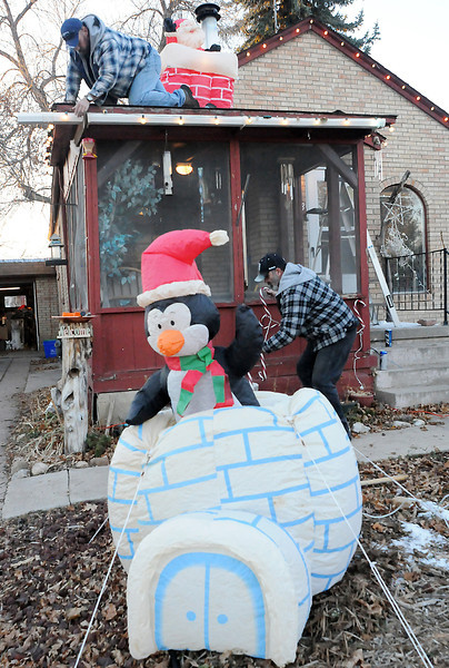 Ian Davis, top, and Cliff Morris hang Christmas lights and candy cane decorations on their house Tuesday afternoon in the 1200 block of Garfield Avenue in Loveland. The holiday display also includes several inflatable decorations including a festive penguin in an igloo, Santa on the roof and a Christmas tree with gifts.