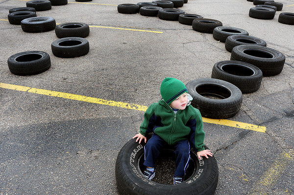"Riley Jones, 2, of Loveland hangs out on the course for the ""Flintstone Car Race"" on Sunday at Orchards Shopping Center."