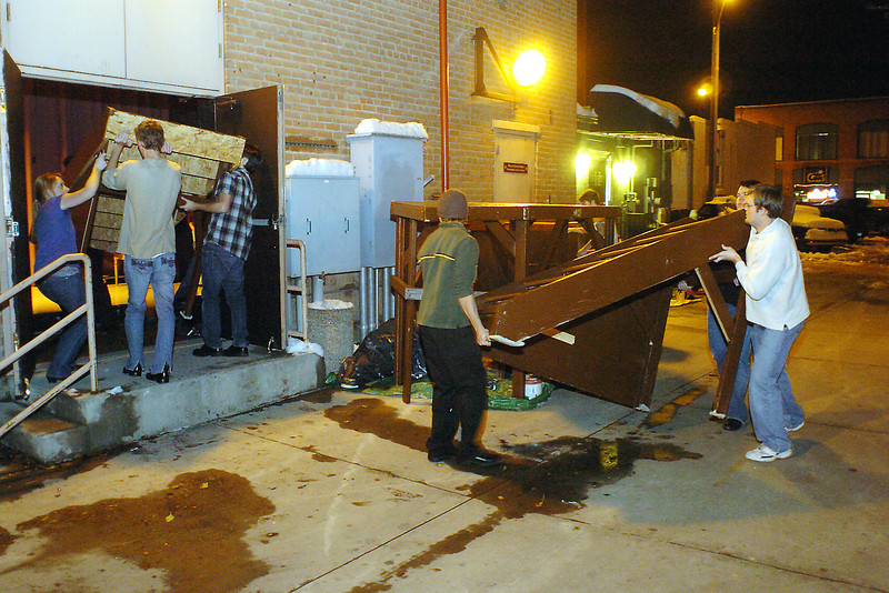 "Cast members from the Up In Lights Productions performance of ""Curtains"" move set pieces onto the stage Thursday evening from the alley behind the Rialto Theater during a rehearsal."