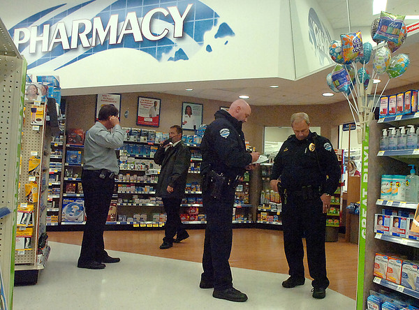 Members of the Loveland Police Department stand near the pharmacy area at the Walgreens at located at Taft Avenue and Southwest 14th Street as they investigate a robbery. From left they are Detective Justin Chase, Detective Scott Highland, Officer Jameson Gartner, and Lt. Tim Brown.