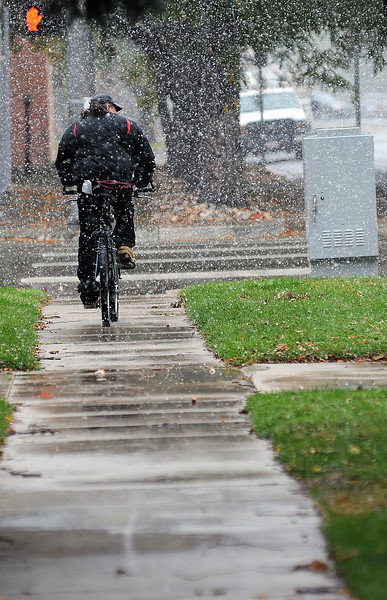 Robert Gregor of Loveland heads east on Sixth Street in downtown as he runs some errands amidst snow flurries on Thursday. Snow fell for much of the day but today is expected to be partly sunny in the morning with highs in the mid-50s and a 20 percent chance of precipitation in the afternoon.